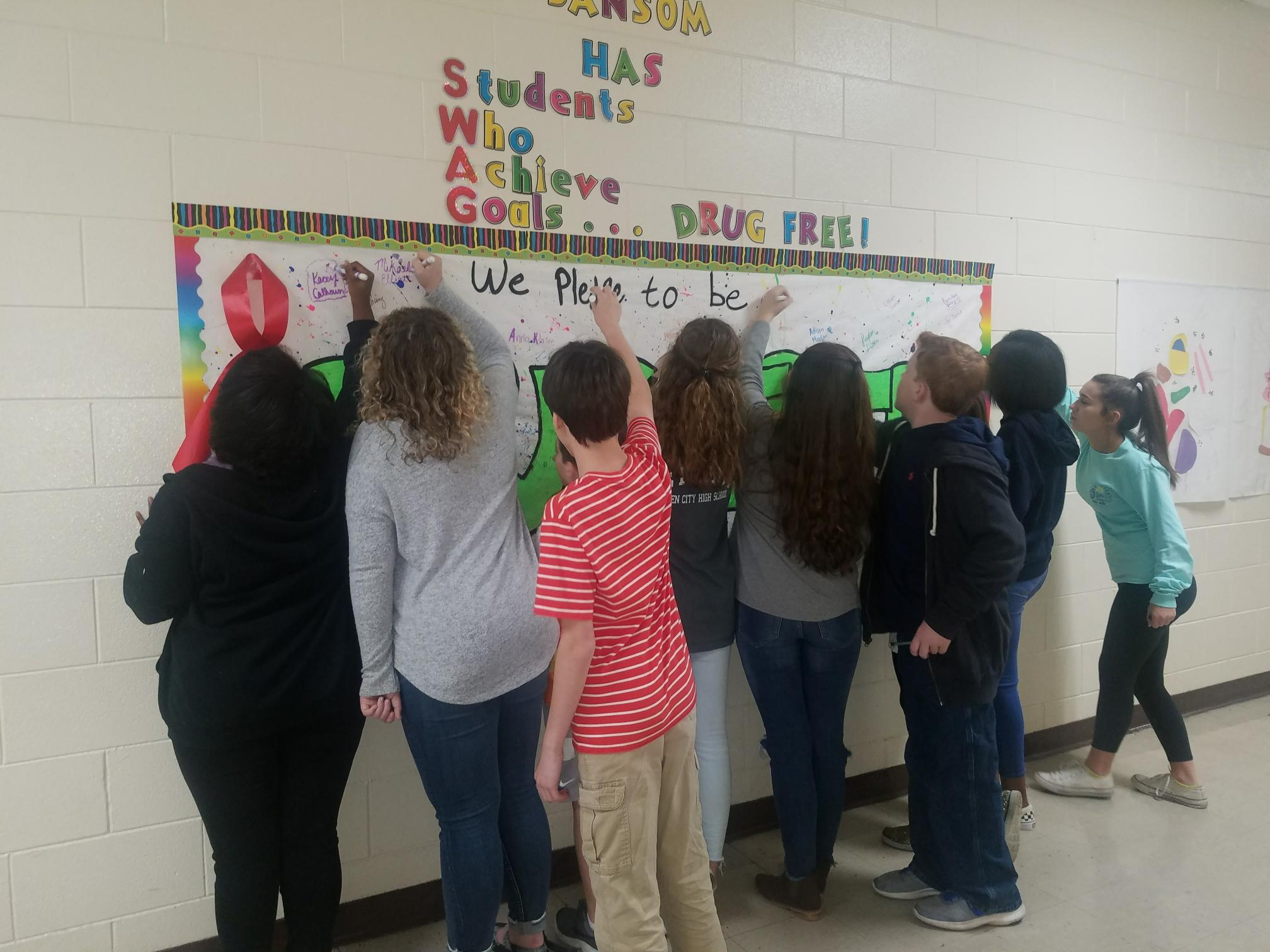 A group of 7th grade students sign pledging to be drug free
