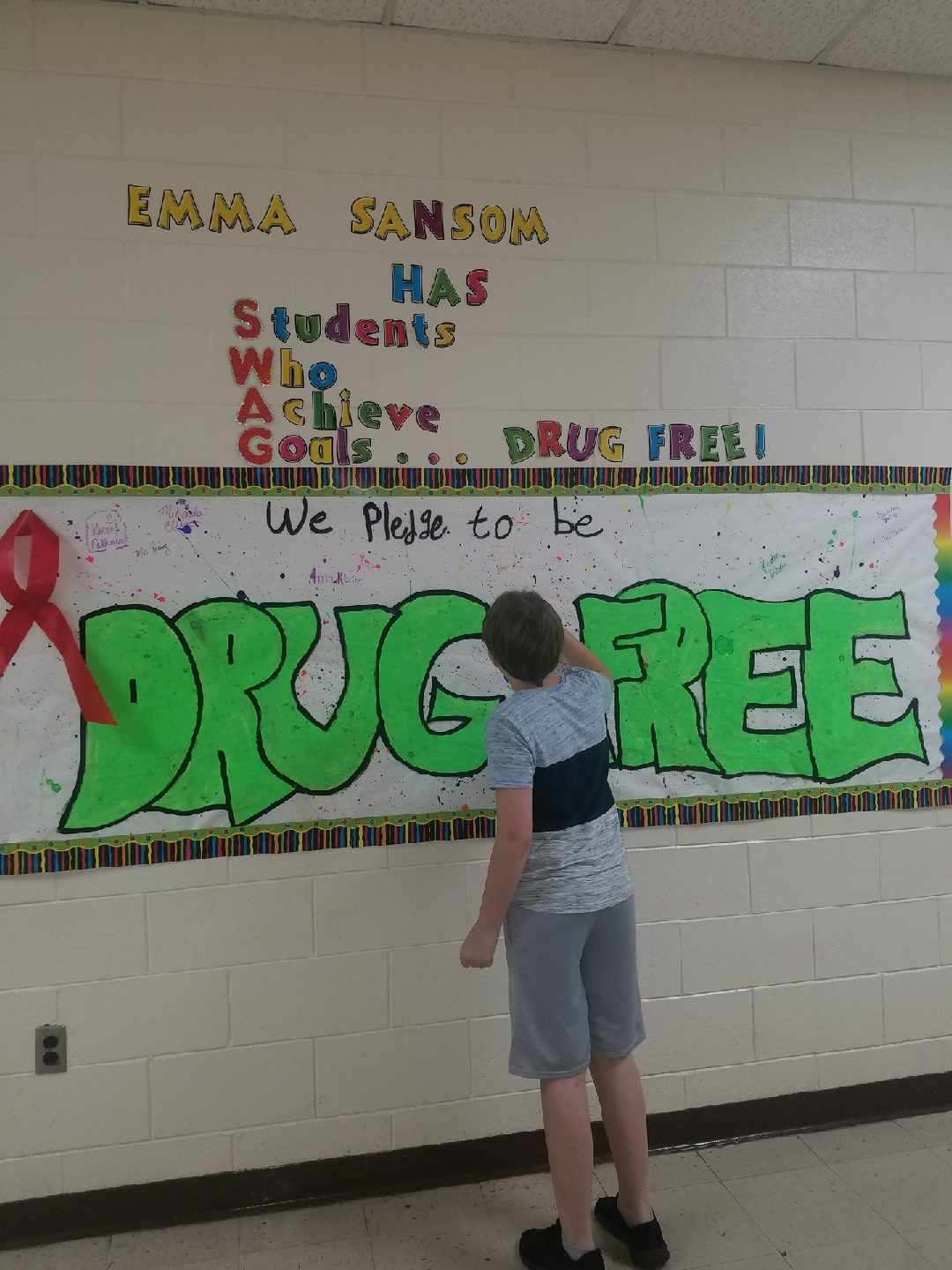 A 7th grade student signs the DRUG FREE pledge sign
